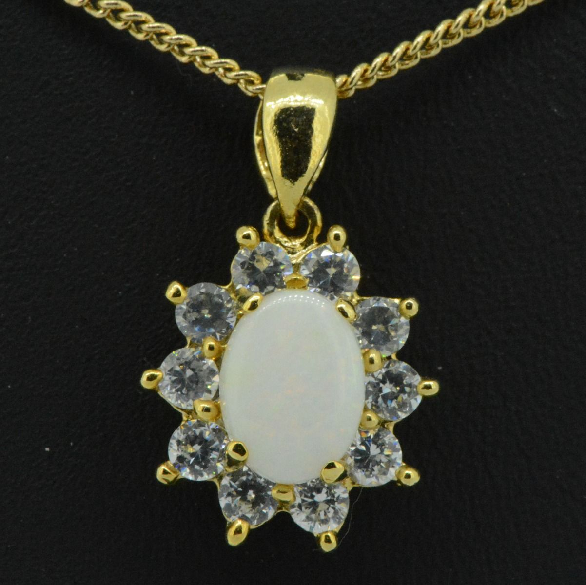 Gold plated solid opal pendant surrounded by cut crystrals