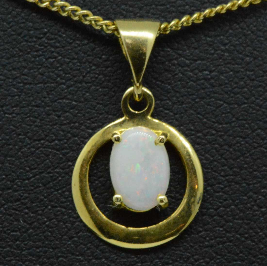 18ct yellow gold circle pendant with a solid opal