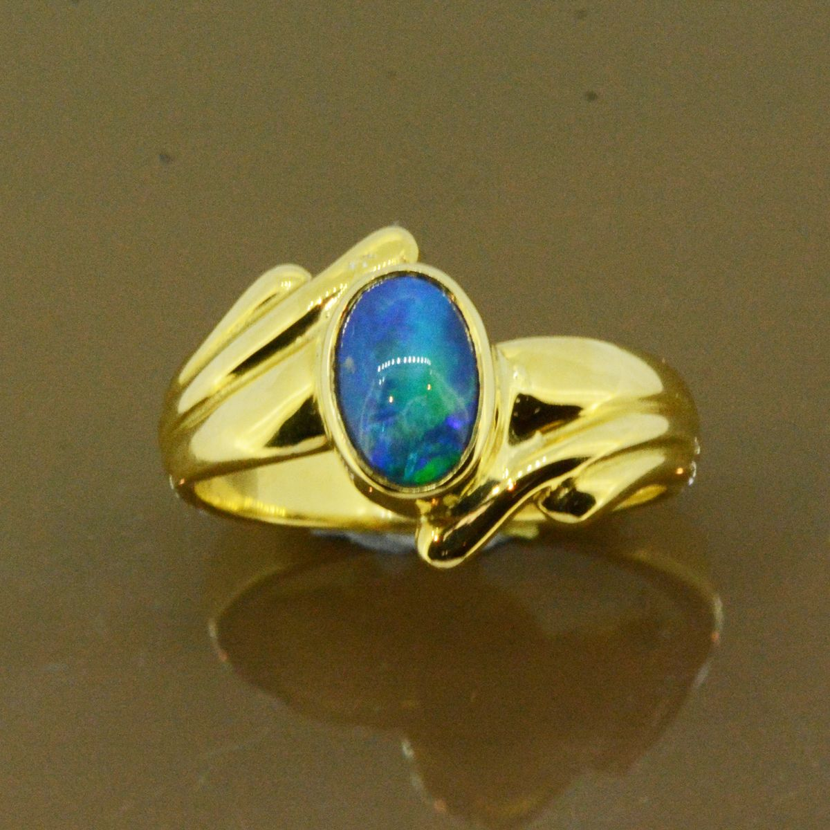 Black opal ring set in 18ct yellow gold (8x6mm)